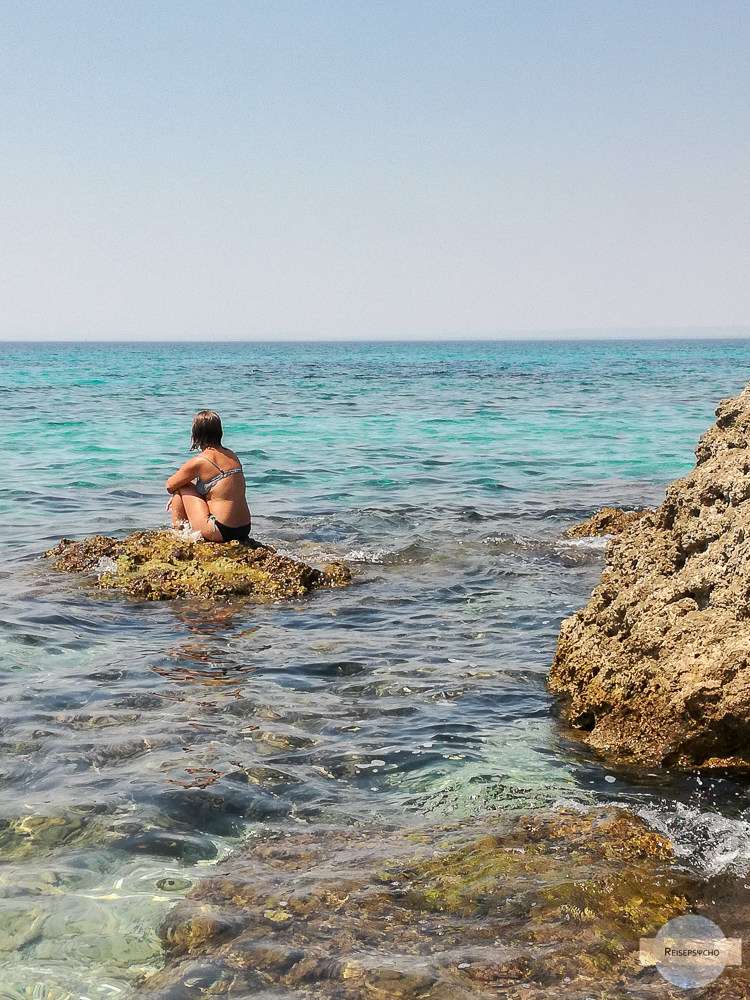 Am Felsen im Wasser sitzen