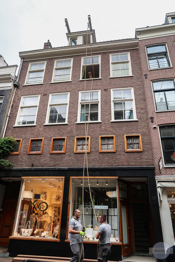 Arbeiter transportieren Material in den obersten Stock in ein Haus in Amsterdam