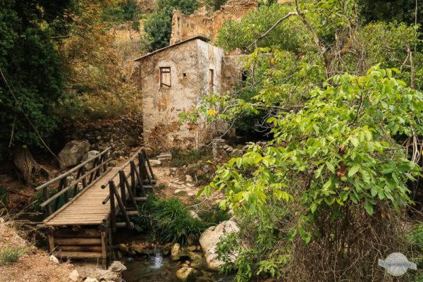 Alte, verfallene Mühle vor einem Bach