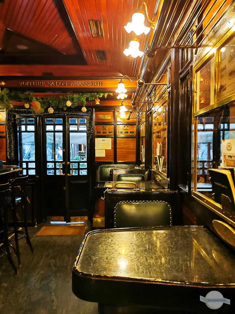 Das Café Orient Express ist eingerichtet wie der alte Zug mit dunklen Möbeln und Holzverschlag