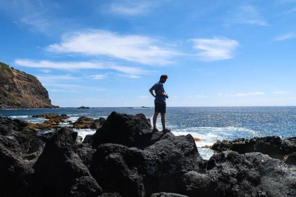 Mann auf Lavasteinen vor dem Meer