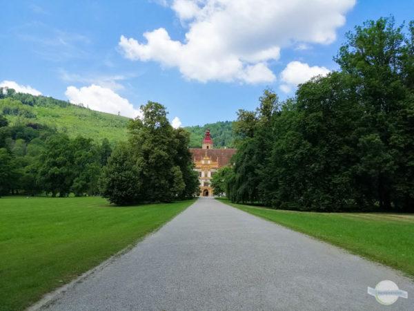 Schloss Eggenberg umringt von Bäumen und einer Allee
